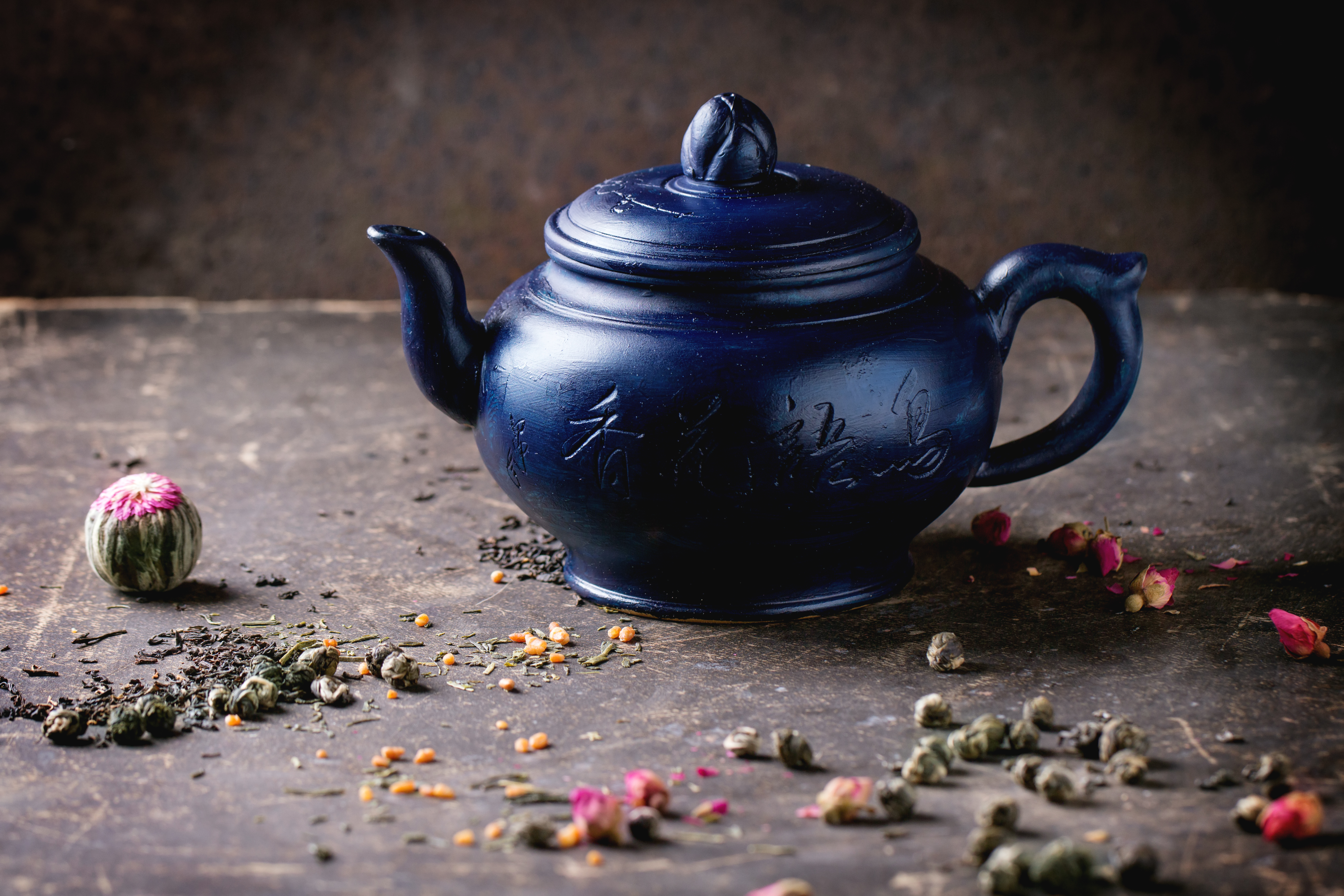 Blue ceramic teapot served with black and green tea lives over dark background